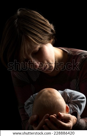 Dark portrait of a loving mother cradling her newborn baby tenderly in her arms as she looks down at it with love and devotion. - stock photo