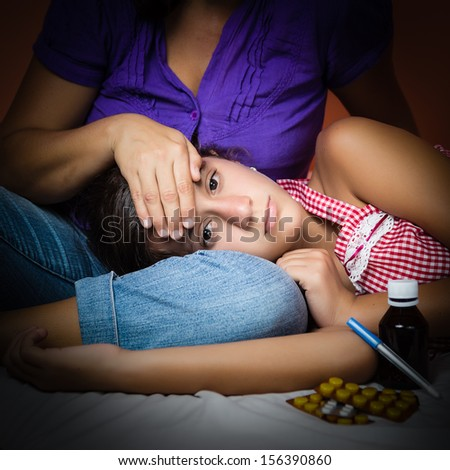 Dark portrait of a sick girl with an adult taking her temperature - stock photo