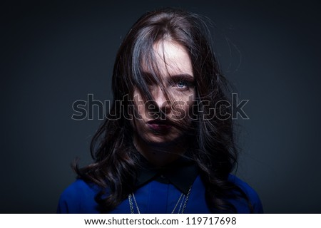 Dark portrait of a woman with hair covering one eye