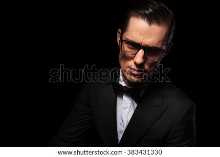 dark portrait of attractive businessman wearing glasses posing in studio background looking at the camera - stock photo