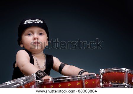 dark portrait of  Beautiful boy playing the drums on a black background