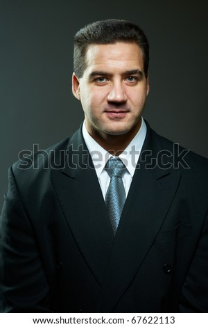 Dark portrait of handsome stylish young man in black suit, studio shot