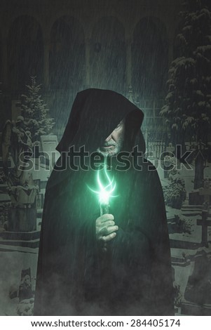Dark portrait of hooded wizard with graveyard background . Fantasy and halloween  - stock photo