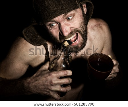 Dark portrait of scary evil sinister bearded man with smirk, he opens a bottle of brandy his teeth . strange Russian man with a naked torso and a woolen hat