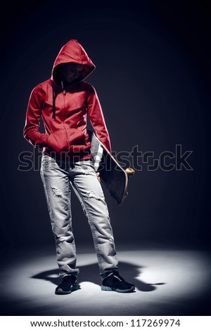 dark portrait of skater standing in spotlight dramatic lighting with red hoodie
