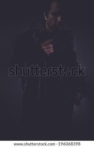 dark portrait of stylish man with long leather jacket, gun armed - stock photo