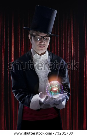 dark portrait of the magician on stage. Holding a luminous sphere. - stock photo