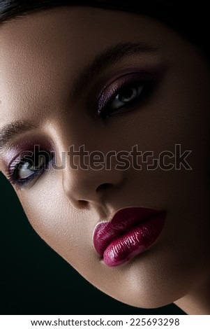 Dark portrait of woman with purple lips close-up - stock photo