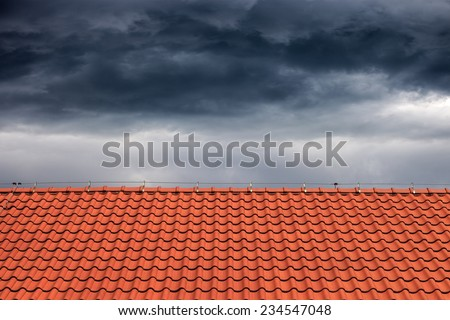 Dark rain clouds above the orange roof.  - stock photo