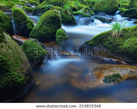 Dark rapid stream with bright blurred blue waves. Big mossy boulders in clear water of mountain river. - stock photo