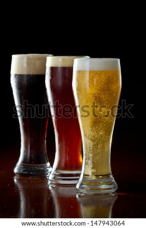 dark, red and light beer served on a dark bar - stock photo