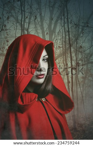 Dark red hooded woman in a misty forest . Fantasy and surreal shot - stock photo