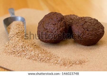 Dark rich and healthy bran muffins sitting on a platter with bran and a small silver serving shovel  - stock photo