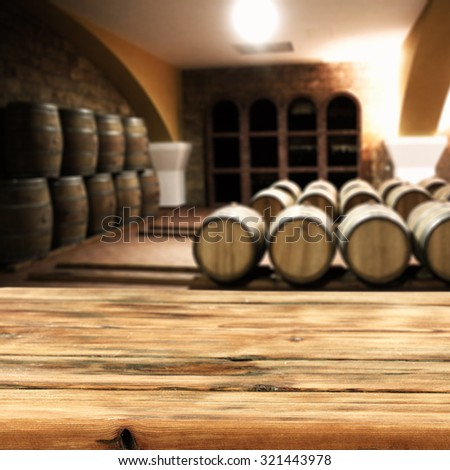 dark room of barrels and wooden desk top and space for you  - stock photo
