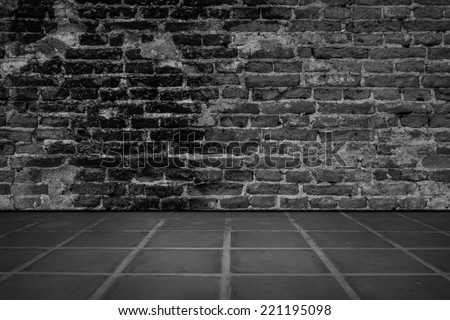Dark room with tile floor and brick wall background. - stock photo