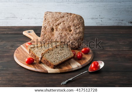 Dark rye homemade bread with cherry tomatoes on round chopping board and copy space