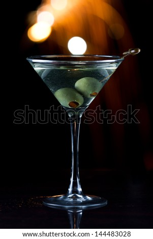 dark scene with a martini glass at night with fireworks in the background