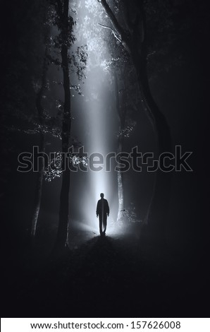 dark scene with man silhouette in forest at night - stock photo