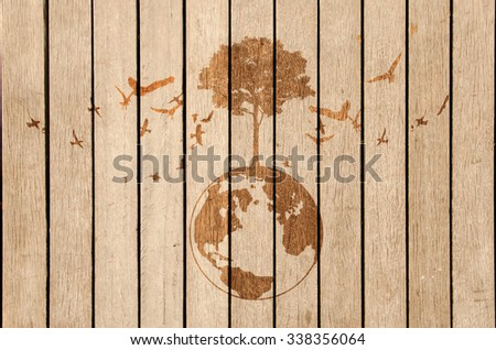 dark shadow of growing tree plant on earth sphere map graphic around with flying birds, on light brown wooden background. ecology concept - stock photo