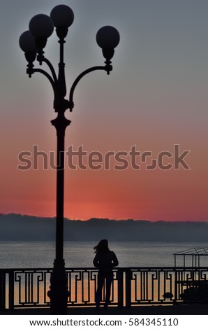 Dark silhouette of a girl at seafront on sunrise sky background with copy space