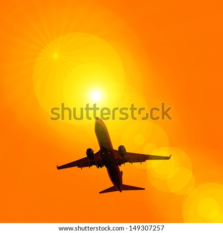 dark silhouette of airplane flying over the orange sky at sunset background