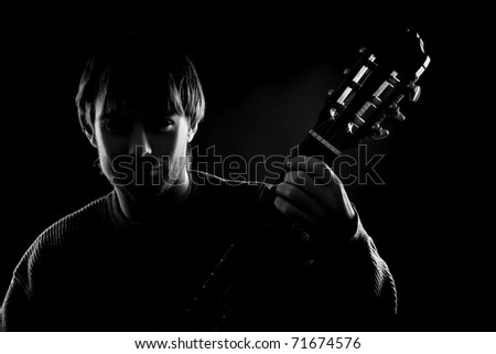 Dark silhouette of guitarist with guitar in darkness. Black and white - stock photo