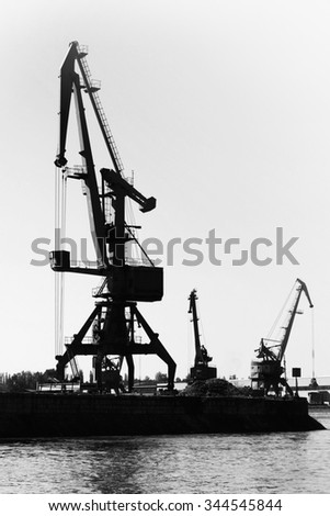 Dark silhouettes of industrial port cranes. Danube River coast in Bulgaria. Black and white vertical photo - stock photo