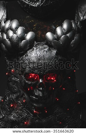 Dark silver armor skull with red eyes and led lights, helmet metal filigree - stock photo