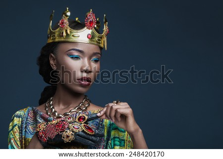 dark-skinned girl in a massive jewelry with exotic makeup - stock photo