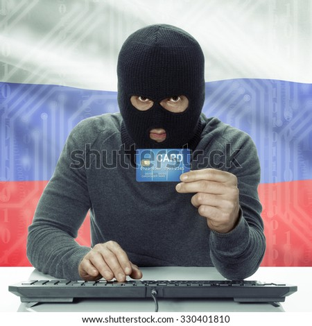 Dark-skinned hacker with credit card in hand and flag on background - Russia