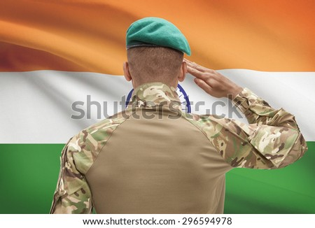 Dark-skinned soldier in hat facing national flag series - India - stock photo