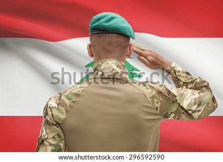Dark-skinned soldier in hat facing national flag series - Lebanon - stock photo