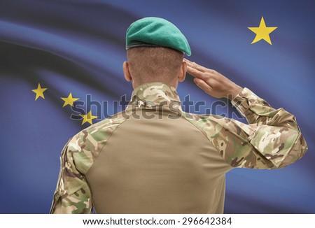 Dark-skinned soldier in hat facing US state flag series - Alaska - stock photo