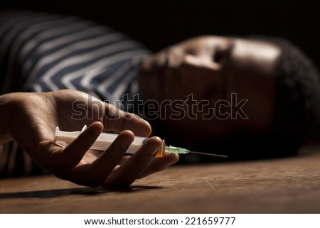 dark-skinned young man lying on the floor with a syringe in her hand
