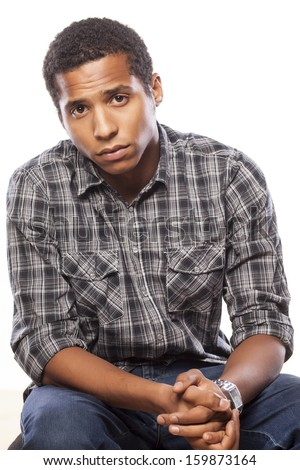 dark-skinned young man posing with a sad expression on white background - stock photo