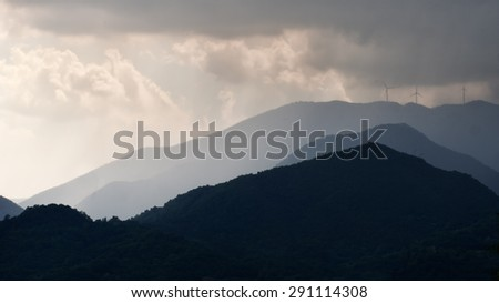 Dark sky and clouds over wind farm, turbines. - stock photo