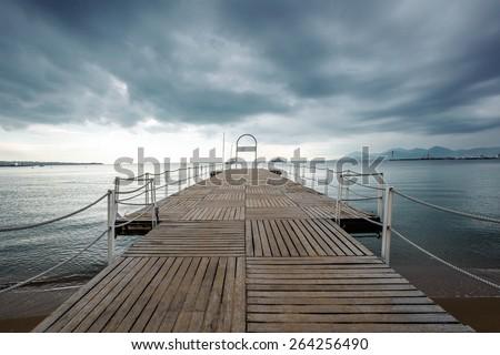 Dark sky over pier in Cannes - stock photo