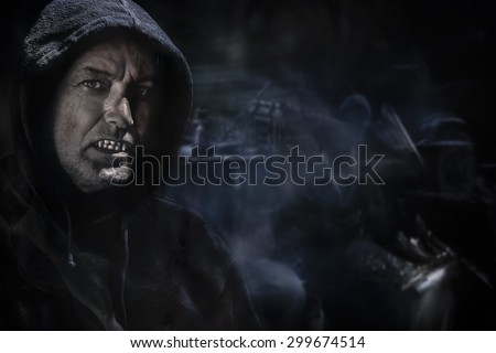 dark smoky horror background with a scary old male tusked vampire  - stock photo