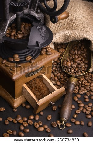 dark still life with coffee and coffee grinder on black background - stock photo