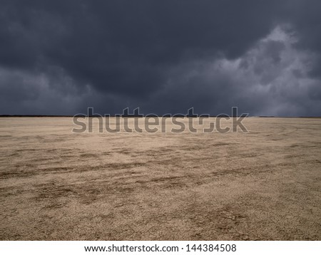 Dark storm clouds at El Mirage dry lake in California's Mojave Desert. - stock photo