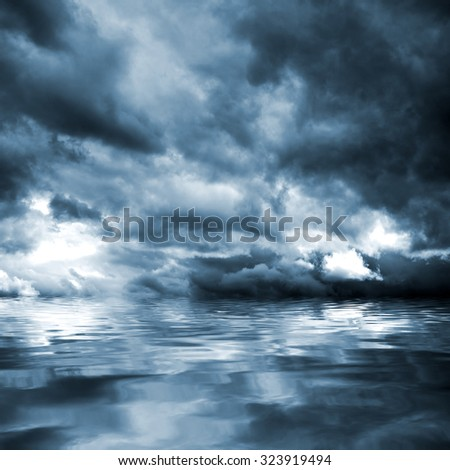Dark storm clouds before rain above the water level. Natural background. - stock photo