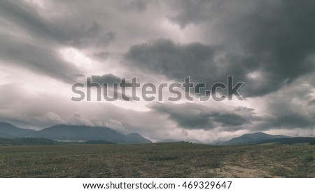 Dark storm clouds over meadow with green grass and mountains in background - vintage effect