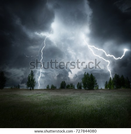 Dark storm clouds over meadow with green grass and trees.