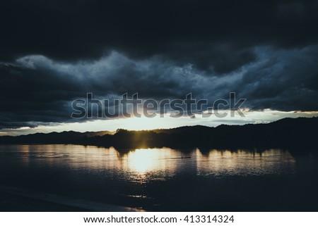 Dark storm sky over the night river. - stock photo
