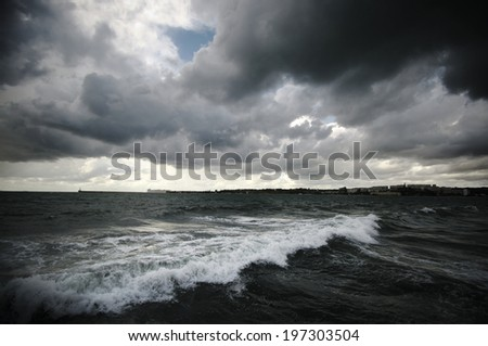 Dark stormy clouds and sea. - stock photo