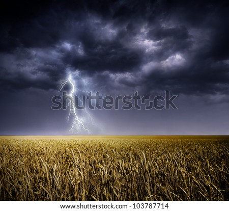 Dark stormy clouds over a field - stock photo