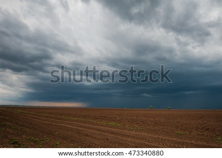 Dark stormy clouds over plow in late april.