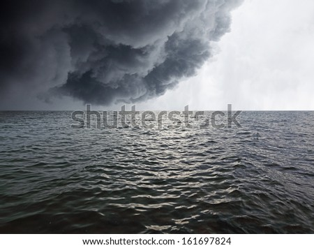 Dark stormy rain cloud in the horizon of a wavy sea.   - stock photo