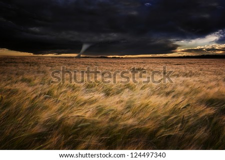 Dark stormy skies over Summer landscape with twister tornado touching down - stock photo