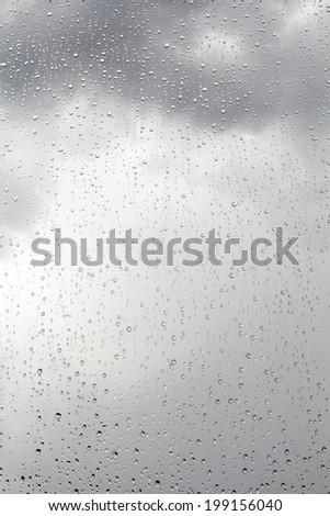 Dark stormy sky and raindrops on the window glass - stock photo